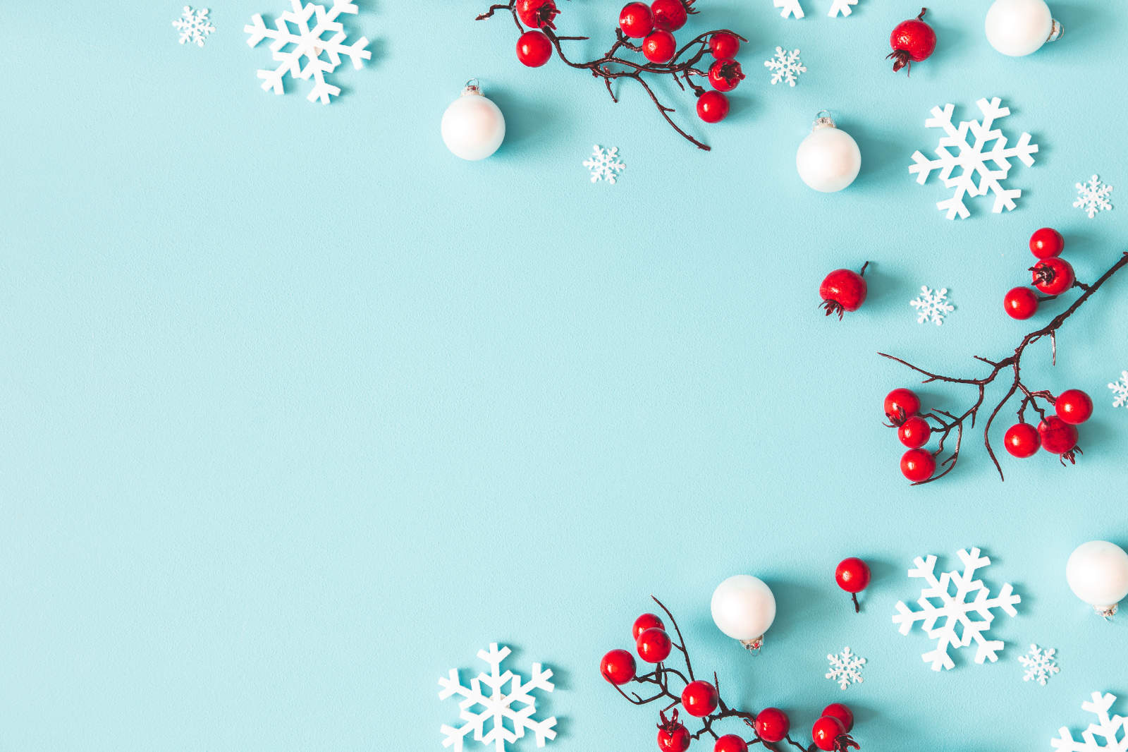 Christmas Snowflakes and red berries on blue background.